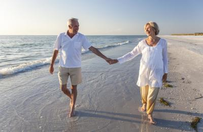 Happy senior couple holding hands and walking on the beach
